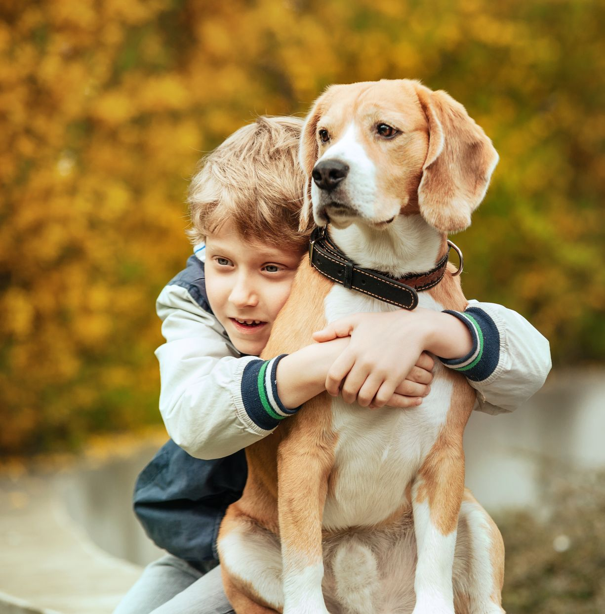 Young boy with arms around dog.
